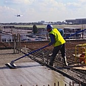Worker uses float after concrete pour on office block at Heathrow Airport, London