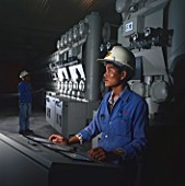Man at control panel in power station, Brunei