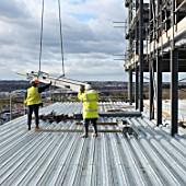 Construction workers receiving steel beams by crane at construction of new supermarket, Milton Keynes, Buckinghamshire, UK