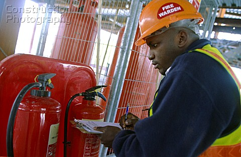 Fire warden checking the fire extinguisher unit on a construction site