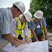 Building technicians looking at plans, Housing development, England.