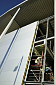 Construction worker upon scaffold, fitting corrugated aluminum cladding on an industrial building.