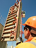 Man talking to tower crane driver through walkie talkie as glass fibre reinforced concrete (GRC) panel is lowered