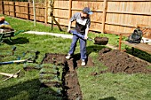 Builder digging a trench in a garden with a spade.