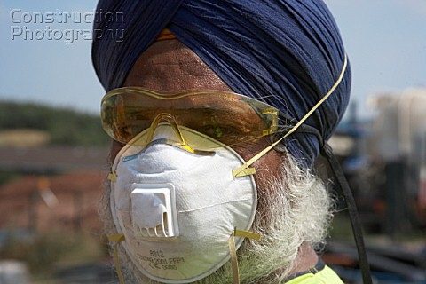 Sikh worker wearing turban and protection mask and goggles UK Sikh workers are allowed not to wear h