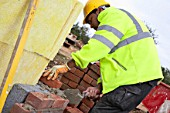 Bricklayer building a cavity wall - house building site, England, UK.
