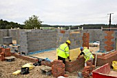Bricklayers on a house building site, England, UK.