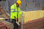 Bricklayer on a house building site, England, UK.