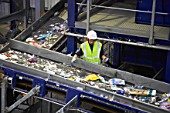 Man sorting recycling on conveyor belt, elevated view