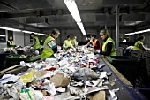 Workers sorting recycling on conveyor belt