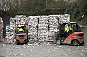 Grip lift truck moving compacted paper recycling bundles at recycling centre