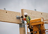 A construction worker guides a wooden joist into position.