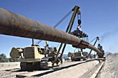 Lifting flexible pipe into trench during construction of pipeline. Barstow, California, USA.