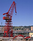 Excavator and harbour crane on site during redevopment of Bilbao waterfront. Spain.