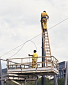 Workers preparing to install overhead power lines for new tram system. Bilbao, Spain, September 2003.