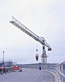 Tower crane lifting concrete hopper over closed footway. Renovation of Tinside swimming pool. Plymouth Hoe, Plymouth, United Kingdom