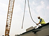 A construction worker attaching a crane cable to a steel beam.