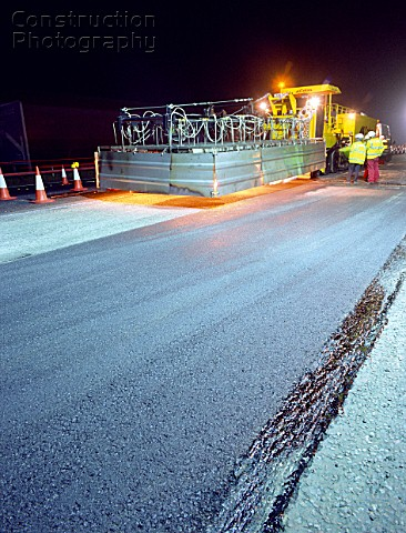 Road surfacing an asphalt Spreader laying tarmac at night
