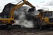Excavator and Dumper Truck moving compost used on contaminated brownfield land, England, United Kingdom