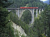 Local train of Rhaetian railway crossing viaduct - Swiss alps - canton of Grisons - Switzerland