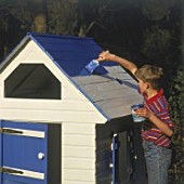 Boy painting self-made wooden house