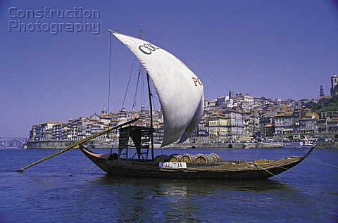 Historic rabelo boat at Douro river carrying port wine in casks city of Porto old town Portugal