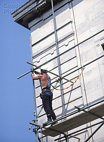 Scaffolder erecting independent scaffolding against face of stone wall using safety harness