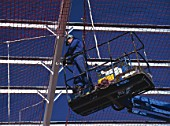 Fixing safety netting to steel frame, prior to roof cladding, using access platform at high level.