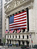 New York Stock Exchange. Neo-classical building covered with the American flag.