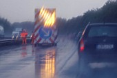 Driving in the rain with motorway maintenance sign