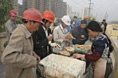 Chinese construction workers buying food on their way to a construction site.