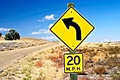Road in Idaho, USA, warning to reduce speed to 20 miles per hour while rounding the curve.