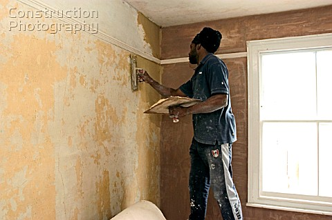 Plasterer skimming a wall