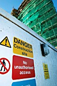 Safety signs on hoarding with Building under construction wrapped with scaffolding and protective sheeting