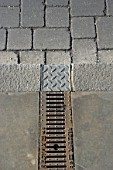 Paving stone with overflow water drain on street pavement