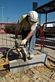 Construction worker sawing a concrete block, UK