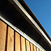 Timber cladded wall supporting a light metal roof, arts and craft shelter at Christchurch Park, Ipswich, UK