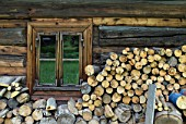 Wood piled around the exterior of a traditional wooden cottage, ready for burning on a stove, Slovakia