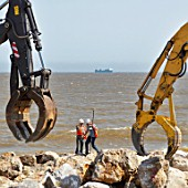 Engineers surveying on the sea defence project at Felixstowe, Suffolk, UK