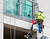 Window cleaner on ropes and suction grips outside an office window