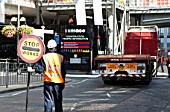 A marshall stopping traffic to allow a lorry to reverse out of a construction site, London Bridge, UK
