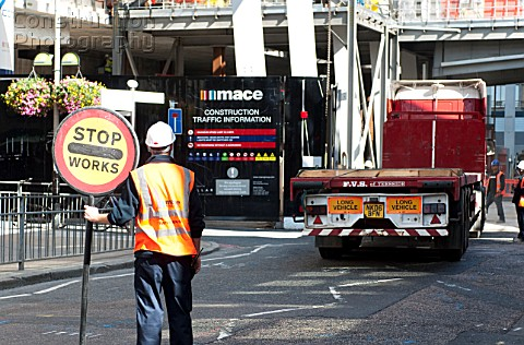 A marshall stopping traffic to allow a lorry to reverse out of a construction site London Bridge UK