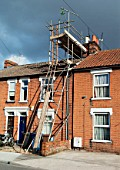 Scaffolding and slide fitted onto a terrace house having a roof tile refit, Ipswich, Suffolk, UK