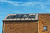 Solar heating panels and skylight windows on a roof top of a residential property, London, UK