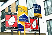 A row of estate agency For Sale boards outside properties.