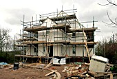 Self build house surrounded by scaffolding