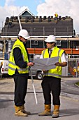 Construction manager and Forman looking at plans on site