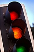 traffic lights showing amber, red and green at a crossroads, UK.