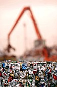 Mechanical digger towers over crushed tin cans in bales at a metal recycling facility on the dockside at a port in Newport, South Wales, UK