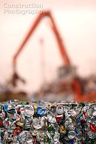 Mechanical digger towers over crushed tin cans in bales at a metal recycling facility on the docksid